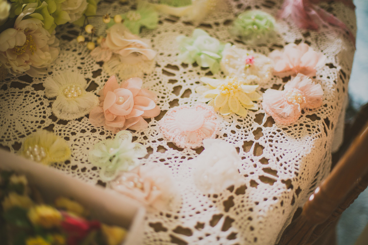 tulle and chiffon flowers sit atop a lace table cloth awaiting the bridal parties use of them